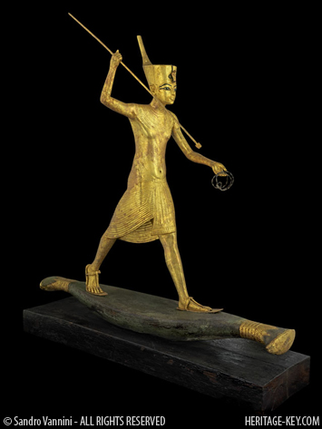 the harpooning king stands with one foot advanced far in front of the other, one heel raised, balancing on his flimsy reed boat, with the harpoon in his right hand and a coil of rope in his left. On his head is the flat crown of Lower Egypt. He wears a broad collar around his neck and a pleated kilt with sporran slung low around his waist, on his feet are sandals. The king here takes the role of Horus, garantor of the divine order, battling the chaotic forces