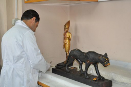 Restorator working on the statue of Tutankhamun standing on a panther. Photo by Stephanie Sakoutis