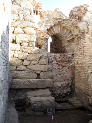The approx. 3 metre high south wall of the heating room of the bathing complex. Warm air was blown under the floor of the middle apsidal space or 'caldarium' (hot water pool).