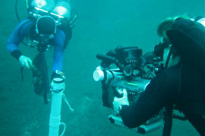 Videographer Marty O'Farrell captures divers taking a core sample from the bottom of pool 6.